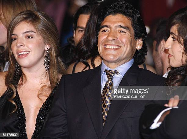 Former Argentinian football player Diego Maradona poses with his daughters of Dalma and Giannina as he arrives to attend the screening of Serbian...
