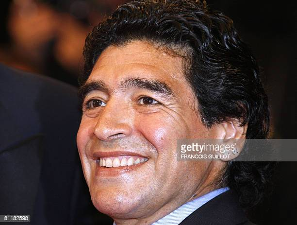 Former Argentinian football player Diego Maradona smiles as he arrives to attend the screening of Serbian director Emir Kusturica's documentary film...
