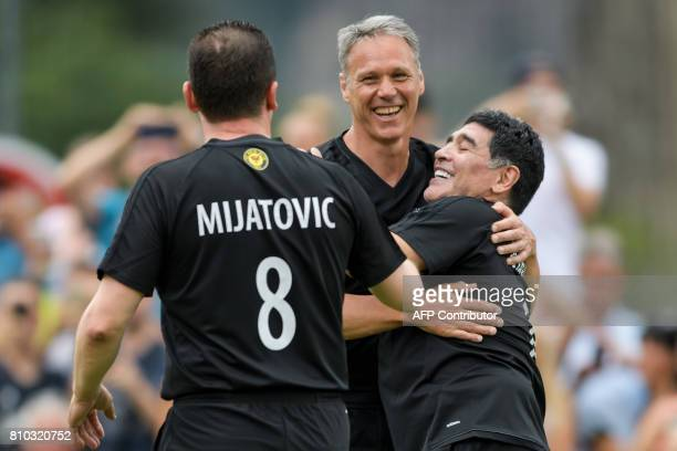 Former Argentinian football star Diego Maradona is congratulated by former Dutch football player Marco van Basten after he scored a goal during 'The...