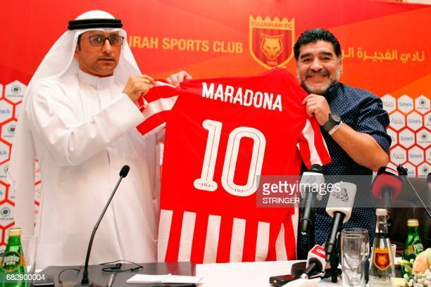 Former Argentinian footballer and manager Diego Armando Maradona holds a jersey of the football club Fujairah FC bearing his name on the reverse...