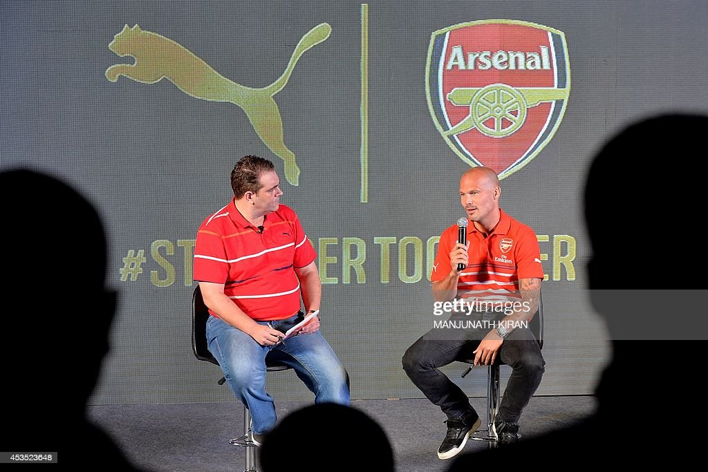 Former Arsenal footballer, Fredrick Ljungberg of Sweden (R) along with a host takes part in an interactive session with the team fans during the launch of Arsenal Football Club kits in Bangalore on August 12, 2014. Fredrick, who is the brand ambassador for Arsenal Soccer Schools, launched sports brand Puma's Arsenal Home, Away And Cup Kits for 2014/15 football season in India. AFP PHOTO/Manjunath KIRAN