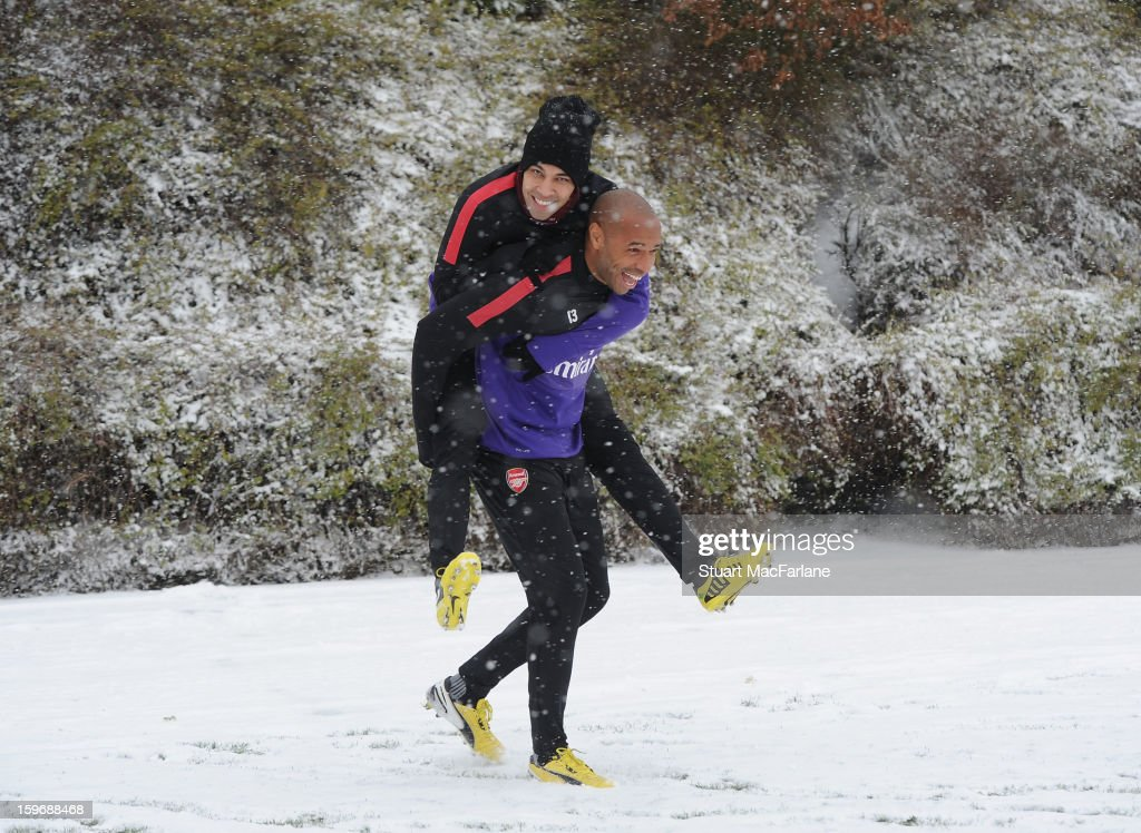 Former Arsenal player Thierry Henry laughs with Andre Santos of Arsenal before a training session at London Colney on January 18, 2013 in St Albans, England.