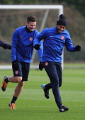 Former Arsenal player Thierry Henry warmsup with Olivier Giroux of Arsenal during a training session at London Colney on November 25 2013 in St...