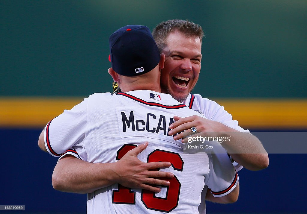 Former Atlanta Brave Chipper Jones hugs Brian McCann #16 of the Atlanta Braves after he threw out the ceremonial first pitch prior to the game against the Philadelphia Phillies during Opening Day at Turner Field on April 1, 2013 in Atlanta, Georgia.