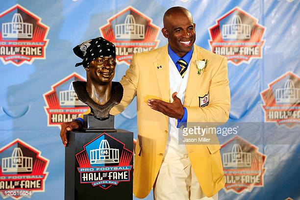 Former Atlanta Falcons cornerback Deion Sanders poses with his bust at the Enshrinement Ceremony for the Pro Football Hall of Fame on August 6 2011...