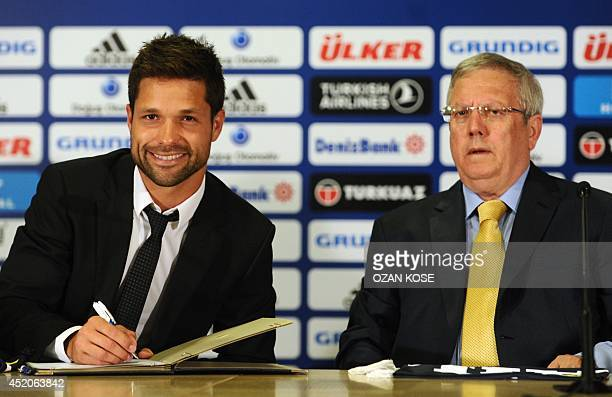 Former Atletico Madrid's Brazilian midfielder Diego Ribas signs his new contract next to Fenerbahce Football Club's President Aziz Yildirim on July...