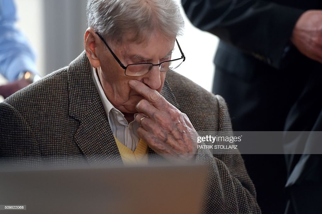 Former Auschwitz guard Reinhold Hanning gestures as he waits for the start of his trial at a court in Detmold, western Germany, on February 11, 2016. The 94-year-old man is charged with at least 170,000 counts of accessory to murder in his role as a former guard at the Nazi concentration camp in occupied Poland. / AFP / POOL / PATRIK STOLLARZ