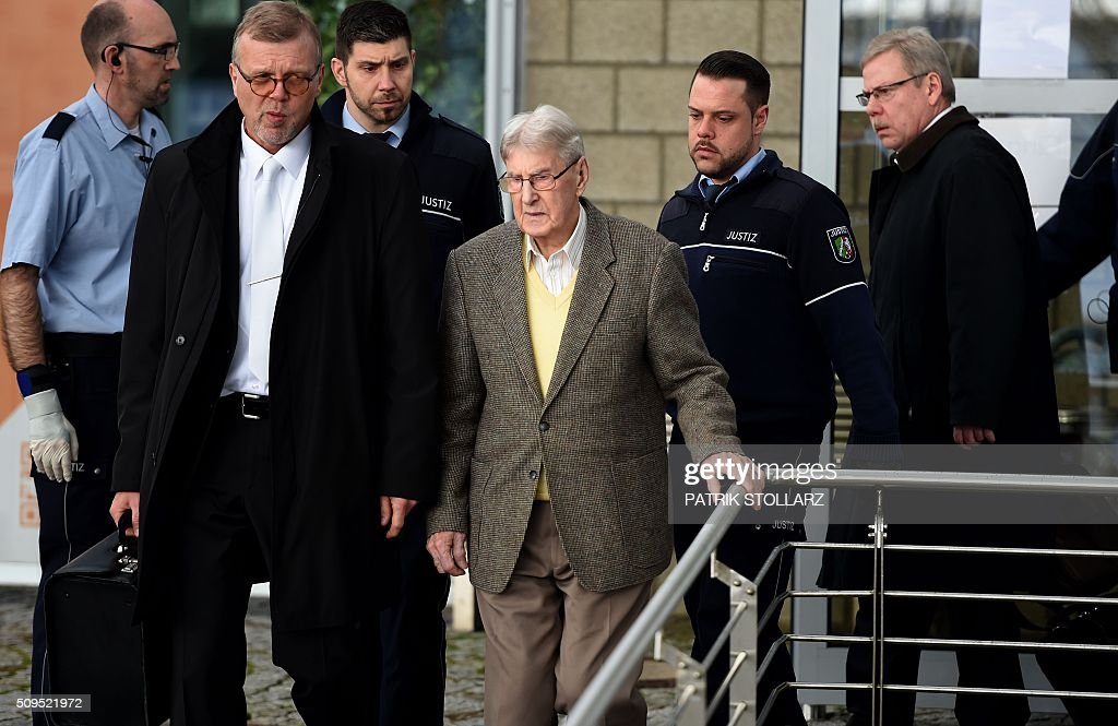 Former Auschwitz guard Reinhold Hanning (C) leaves the court after the start of his trial in Detmold, western Germany, on February 11, 2016. The 94-year-old man is charged with at least 170,000 counts of accessory to murder in his role as a former guard at the Nazi concentration camp in occupied Poland. / AFP / PATRIK STOLLARZ