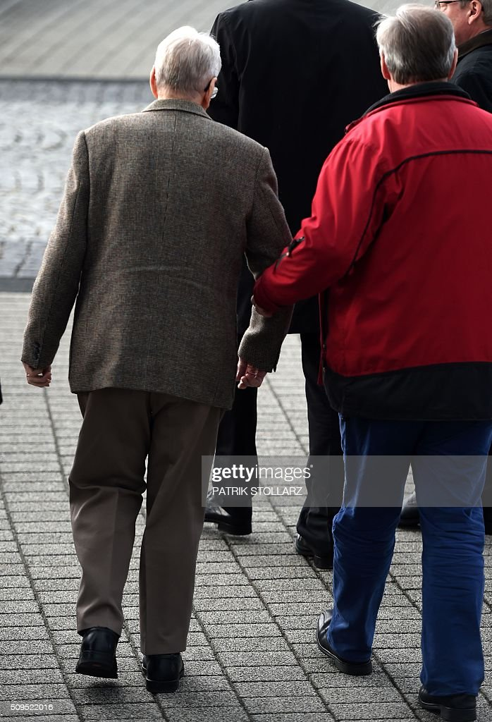 Former Auschwitz guard Reinhold Hanning (L) leaves the court after the start of his trial in Detmold, western Germany, on February 11, 2016. The 94-year-old man is charged with at least 170,000 counts of accessory to murder in his role as a former guard at the Nazi concentration camp in occupied Poland. / AFP / PATRIK STOLLARZ