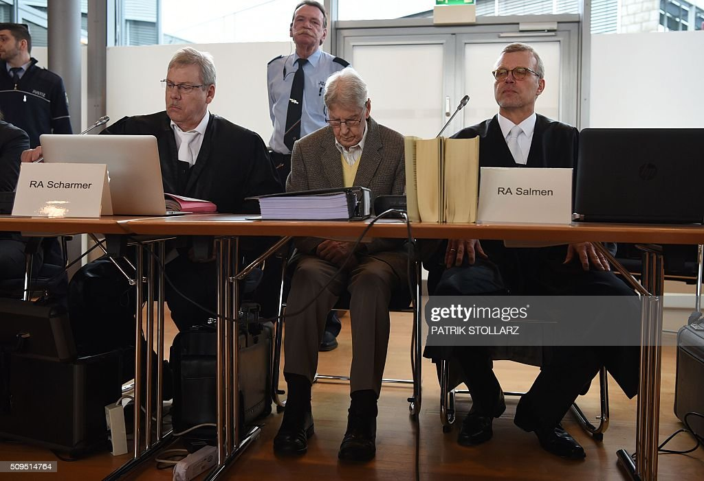 Former Auschwitz guard Reinhold Hanning (C) sits between his lawyers as he waits for the start of his trial at court in Detmold, western Germany, on February 11, 2016. The 94-year-old man is charged with at least 170,000 counts of accessory to murder in his role as a former guard at the Nazi concentration camp in occupied Poland. / AFP / PATRIK STOLLARZ