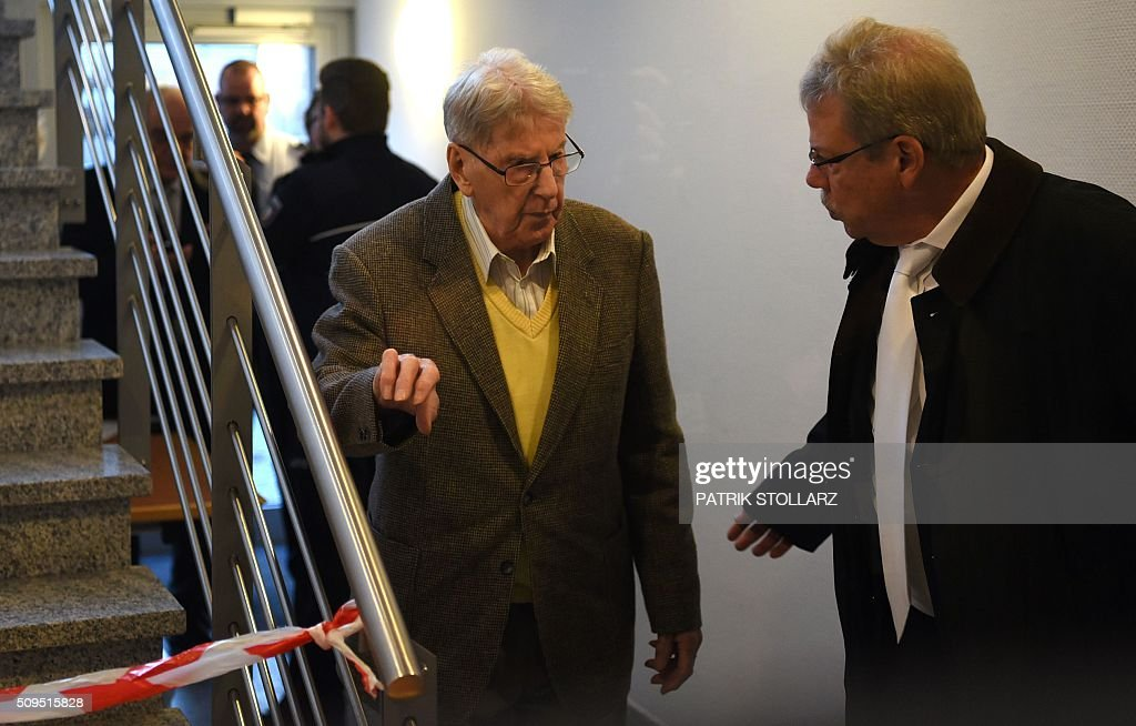 Former Auschwitz guard Reinhold Hanning (C) speaks with his lawyer Andreas Scharmer (R) as he arrives for his trial at court in Detmold, western Germany, on February 11, 2016. The 94-year-old man is charged with at least 170,000 counts of accessory to murder in his role as a former guard at the Nazi concentration camp in occupied Poland. / AFP / PATRIK STOLLARZ
