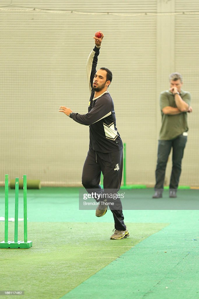 Former Australia cricket player Stuart MacGill (R) watches on as Victorian player Fawad Ahmed bowls during a meeting at the Sydney Cricket Ground Indoor Nets on March 28, 2013 in Sydney, Australia.