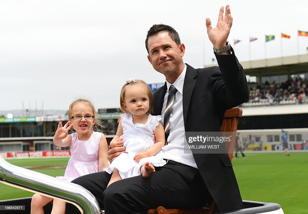 Former Australian batsman Ricky Ponting waves to the crowd as he does a lap of honour with his daughters Emmy (L) and Matisse (2/L) on the first day of the first cricket Test match, in Hobart on December 13, 2012. AFP PHOTO/William WEST IMAGE