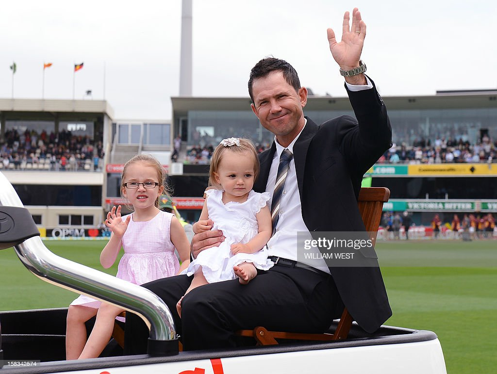 Former Australian batsman Ricky Ponting waves to the crowd as he does a lap of honour with his daughters Emmy (L) and Matisse (2/L) on the first day of the first cricket Test match, in Hobart on December 14, 2012. AFP PHOTO/William WEST IMAGE RESTRICTED TO EDITORIAL USE - STRICTLY NO COMMERCIAL USE