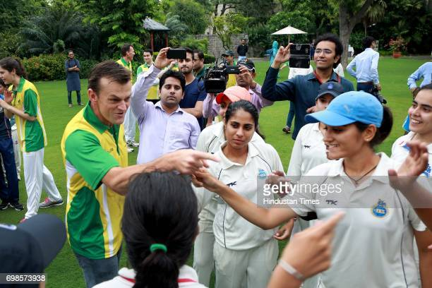 Former Australian Cricketer Adam Gilchrist poses with the players of the winning team during the fiveover friendly match between Education All Stars...