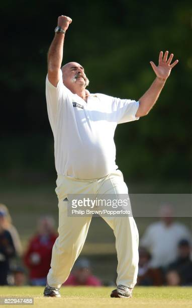 Former Australian cricketer Merv Hughes celebrates after taking a hattrick of wickets during a charity match between Shane Warne's Australia XI and...