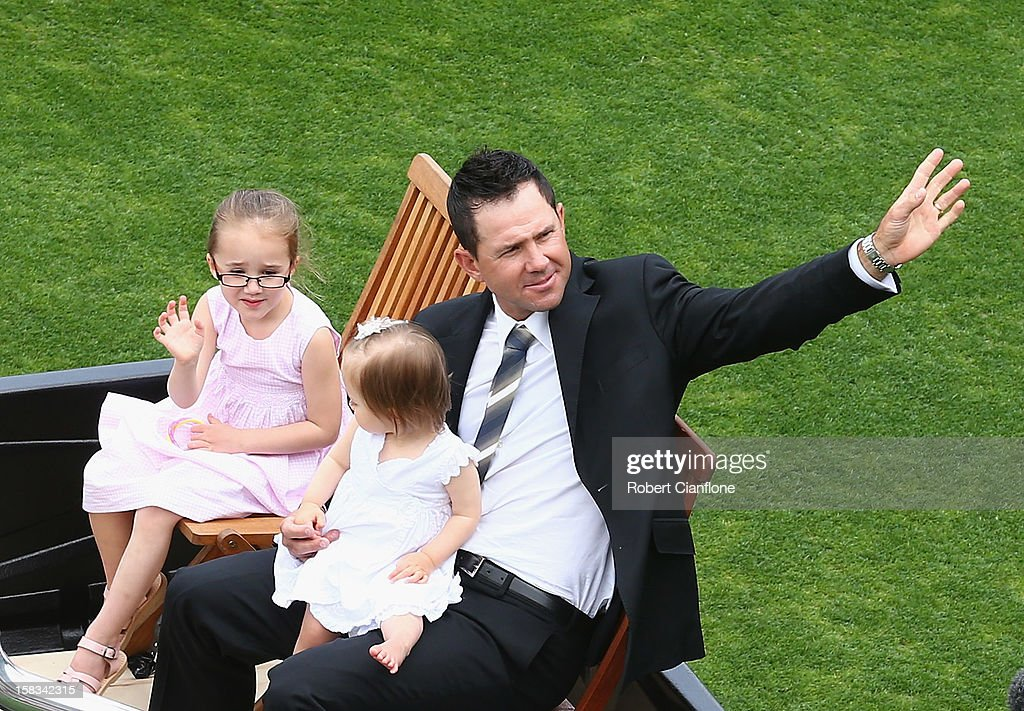 Former Australian cricketer Rick Ponting waves to the crowd on a farewell lap with his daughters Emmy and Matisse during day one of the First Test match between Australia and Sri Lanka at Blundstone Arena on December 14, 2012 in Hobart, Australia.