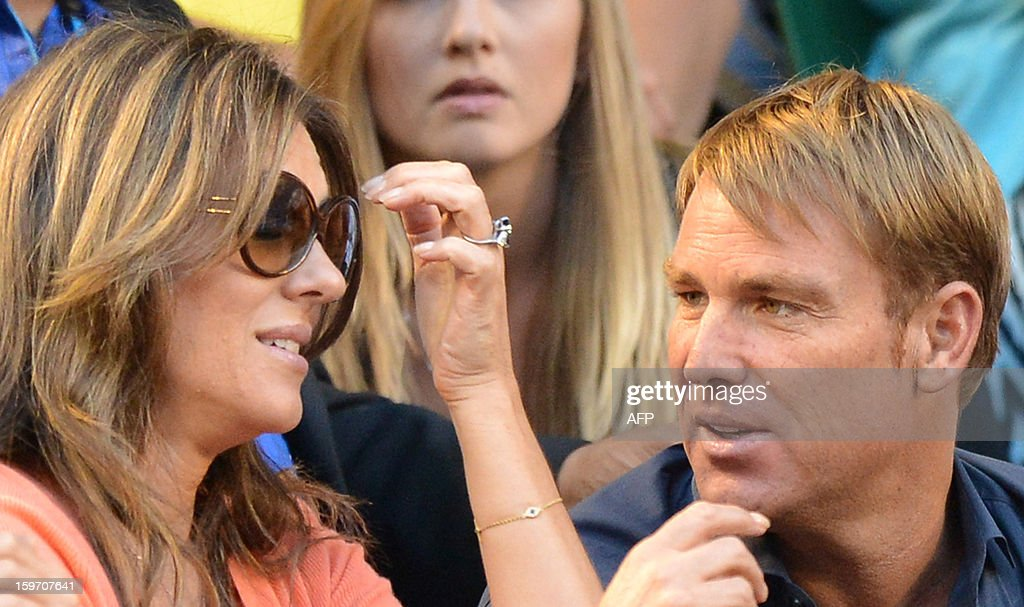 Former Australian cricketer Shane Warne (R) and British actress Elizabeth Hurley speak as Switzerland's Roger Federer plays during his men's singles match against Australia's Bernard Tomic on the sixth day of the Australian Open tennis tournament in Melbourne on January 19, 2013.