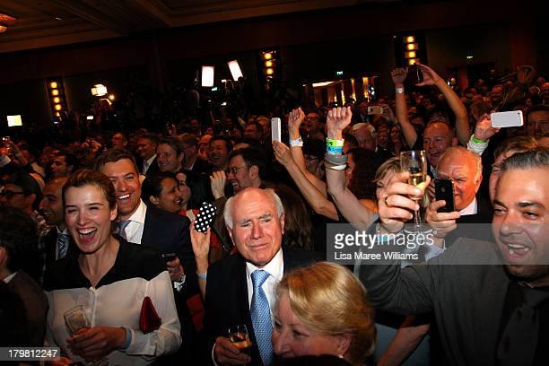 Former Australian PM John Howard celebrates as Australian Prime Ministerelect Tony Abbott claims victory in the 2013 Australian Election on September...