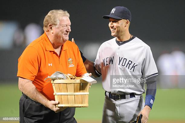 Former Baltimore Orioles player Boog Powell presents Derek Jeter of the New York Yankees with a basket of crabs as a farewell gift for his last game...