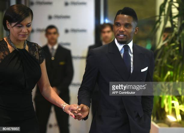 Former Barcelona player Cameroonian Samuel Eto'o and his wife walk on a red carpet upon arrival to attend Argentine football star Lionel Messi and...