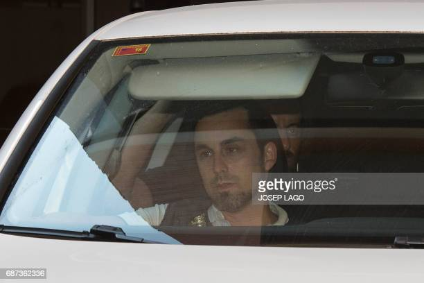 Former Barcelona's football club president Sandro Rosell sits behind a policeman in a car leaving his home after being arrested in a money laundering...
