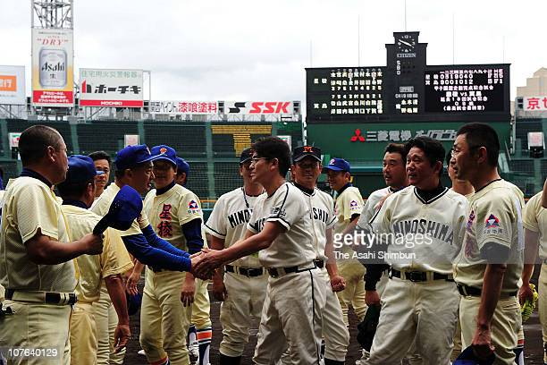 Former baseball players from Minoshima High School and Seiryo High School shake hands after the reunion match at Koshien Stadium on September 23 2010...