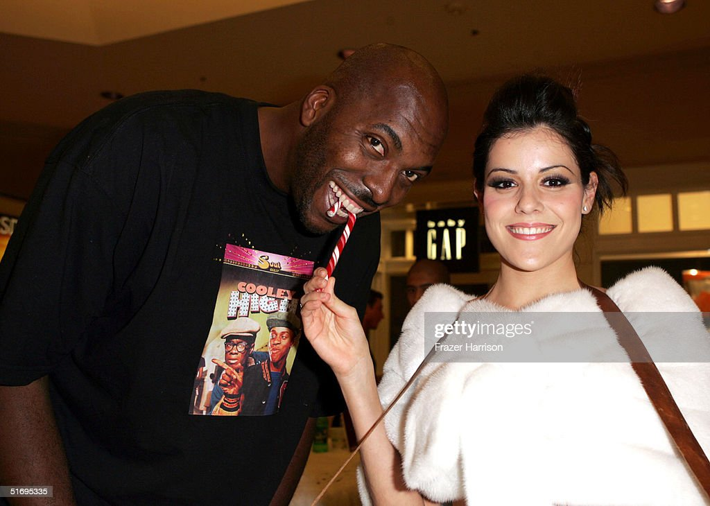 Former Basketball player John Salle poses with Candy Cane girl Sonia Benitez at the Beverly Center's 'Night at the Candy Cane Lounge' chartiy event...