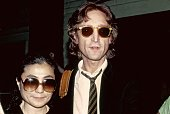 Former Beatle John Lennon and his wife Yoko Ono pose for a portrait outside of the Times Square recording studio 'The Hit Factory' before a recording...