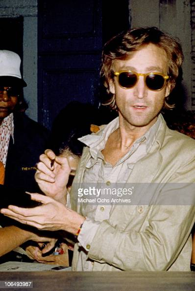Former Beatle John Lennon signs autographs outside the Times Square recording studio 'The Hit Factory' after a recording session of his final album...