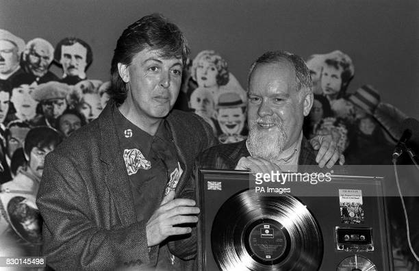 Former Beatle Paul McCartney presents Peter Blake who designed the sleeve of the album Sgt Pepper's Lonely Hearts Club Band with a set of platinum...