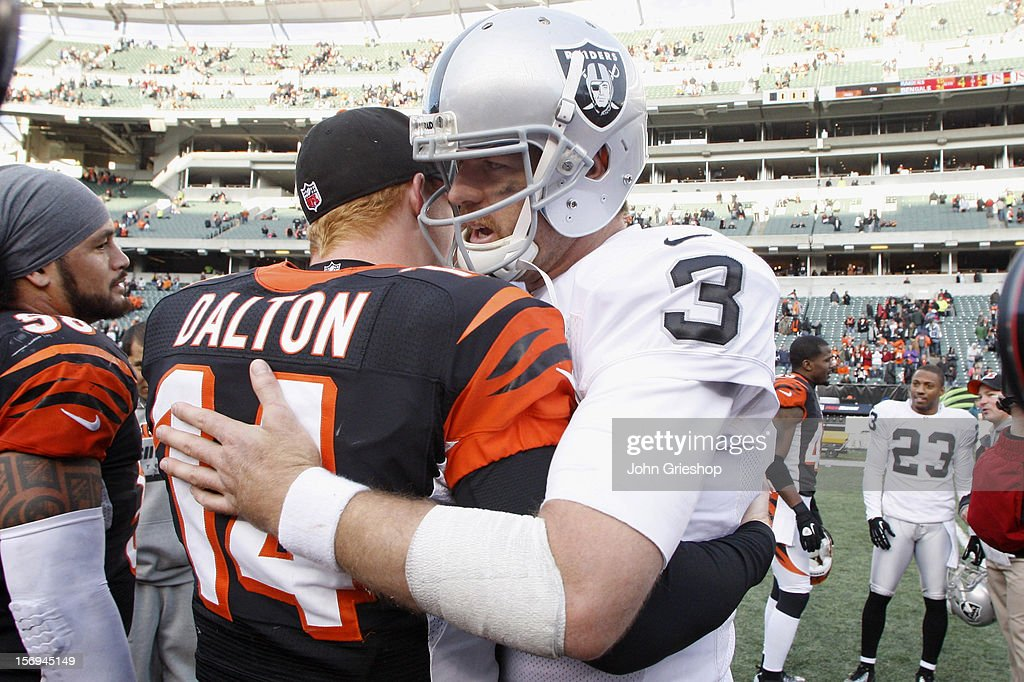Former Bengal <a gi-track='captionPersonalityLinkClicked' href=/galleries/search?phrase=Carson+Palmer&family=editorial&specificpeople=202556 ng-click='$event.stopPropagation()'>Carson Palmer</a> #3 of the Oakland Raiders shares a moment with <a gi-track='captionPersonalityLinkClicked' href=/galleries/search?phrase=Andy+Dalton+-+American+Football+Player&family=editorial&specificpeople=15271549 ng-click='$event.stopPropagation()'>Andy Dalton</a> #14 of the Cincinnati Bengals after their game at Paul Brown Stadium on November 25, 2012 in Cincinnati, Ohio. The Bengals defeated the Raiders 34-10.