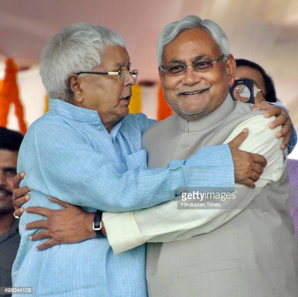 Former Bihar Chief Minister and RJD Chief Lalu Prasad Yadav hugs of JDU leader and Bihar Chief Minister Nitish Kumar during the oath taking ceremony...