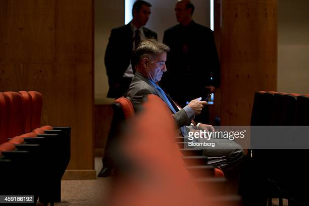 Former billionaire Eike Batista checks a mobile device as waits inside court for the start of his insidertrading trial in Rio de Janeiro Brazil on...