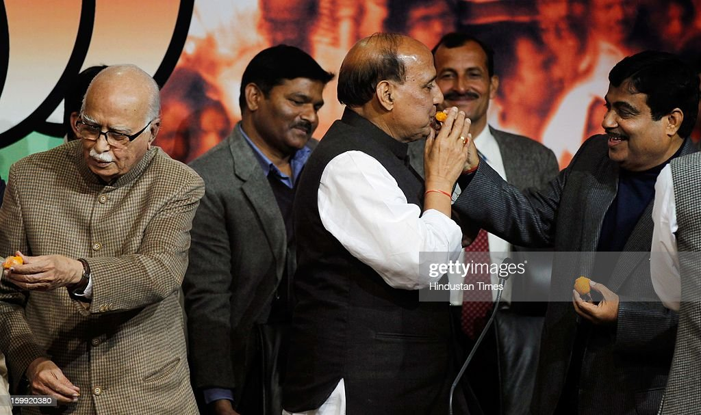 Former BJP President Nitin Gadkari offers sweet to BJP President Rajnath Singh while L K Advani looks on at BJP Headquarter, on January 23, 2012 in New Delhi, India. Rajnath Singh succeeds Nitin Gadkari, who decided against contesting for a second term following charges of alleged corruption.