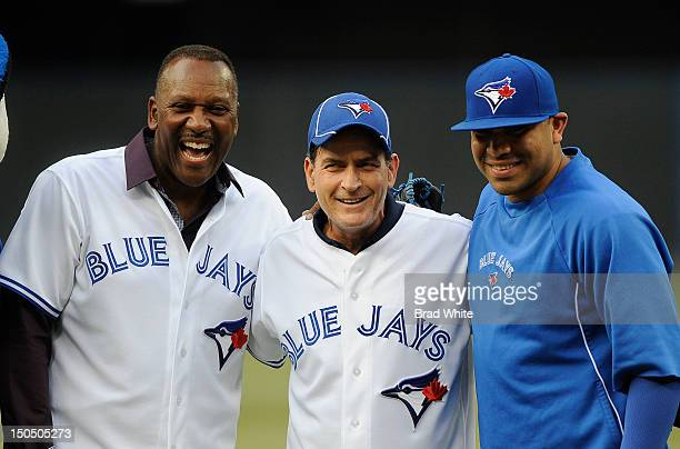 Former Blue Jay Joe Carter Actor Charlie Sheen and Ricky Romero of the Toronto Blue Jays take part in an on field ceremony prior to MLB game action...