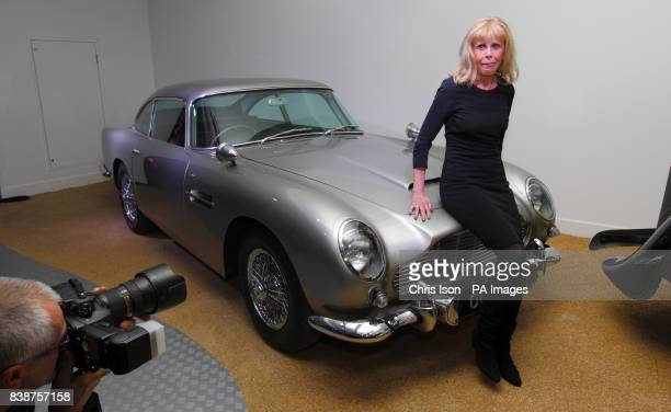 Former Bond girl Britt Ekland sits on the bonnet of the original Aston Martin DB5 at a new exhibition Bond in Motion at the National Motor Museum...