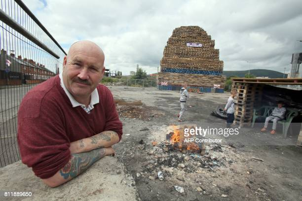 Former Bonfire builder Colin Tweedie poses for a photograph beside a bonfire in the village area of Belfast Northern Ireland on July 10 ahead of the...