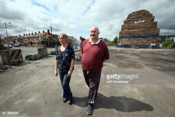 Former Bonfire builder Colin Tweedie walks in front of a bonfire in the village area of Belfast Northern Ireland on July 10 ahead of the traditional...