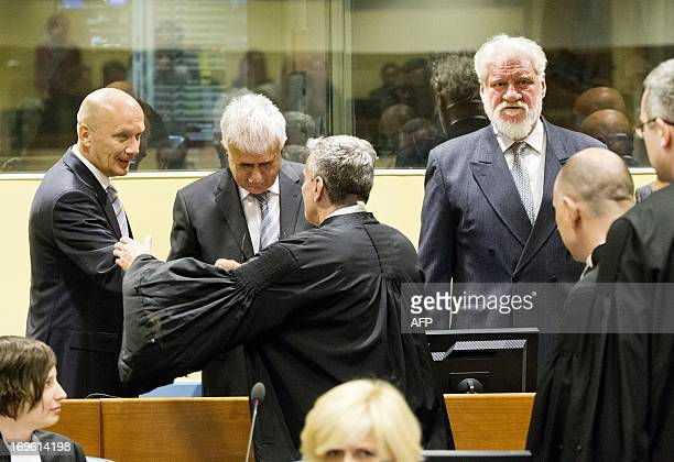Former Bosnian Croat leader Jadranko Prlic shakes hands with his lawyer next to codefendants Bruno Stojic and Slobodan Praljak in the the courtroom...