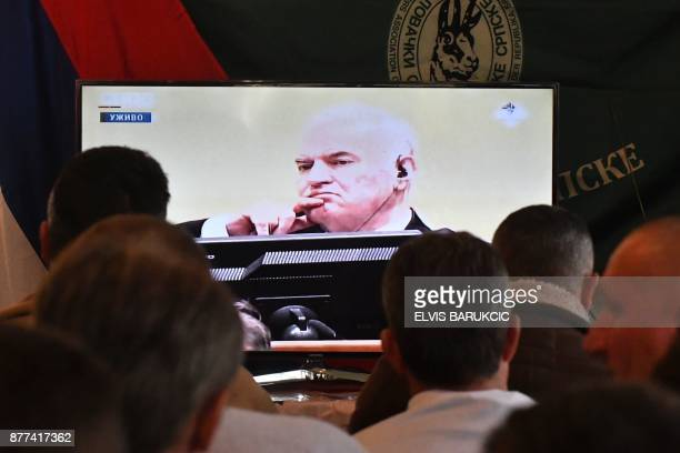 TOPSHOT Former Bosnian Serbian commander Ratko Mladic appears on a TV screen when people gather to watch a live broadcast from the International...