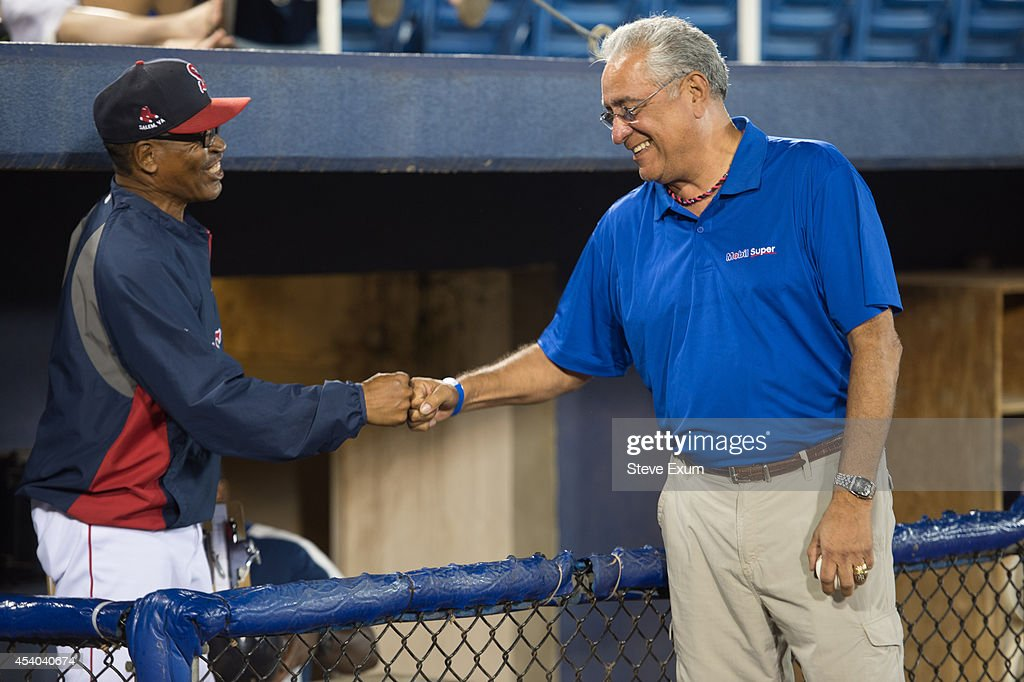 Former Boston Red Sox pitcher Mike Torrez fist bumps with Salem Red Sox hitting coach U.L. Washington following the ceremonial first pitch at Salem Memorial Ballpark August 23, 2014 in Salem, Virginia. Torrez joined the Mobil Super 'Go the Distance' Baseball Tour for the Salem Red Sox game against the Wilmington Blue Rocks.