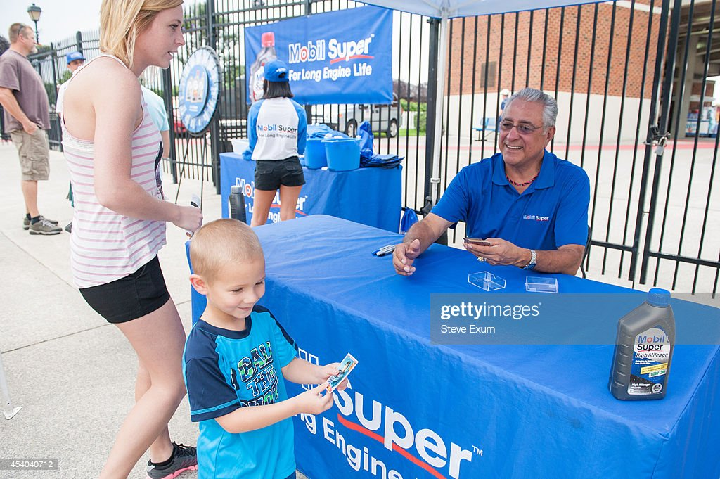 Former Boston Red Sox pitcher Mike Torrez hands one of his signed baseball cards to a Salem Red Sox fan Amir Maiden, 4, outside Salem Memorial Ballpark as part of Mobil Super 'Go the Distance' Baseball Tour August 23, 2014 in Salem, Virginia. Torrez joined the Mobil Super team to meet fans and give away autographed baseballs and other prizes.