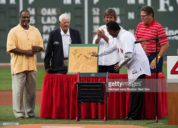 Former Boston Red Sox pitcher Pedro Martinez accepts a gift from Hall of Famers Jim Rice Carl Yastrzemski Dennis Eckersley and Carlton Fisk during a...