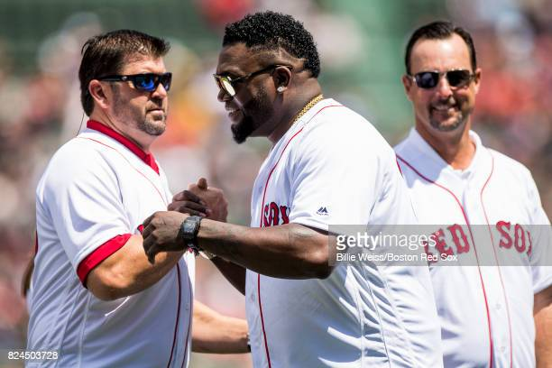 Former Boston Red Sox player David Ortiz high fives Jason Varitek and Tim Wakefield during a 2007 World Series Champion team reunion before a game...