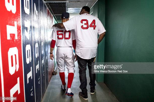 Former Boston Red Sox player David Ortiz walks through a hallway with Mookie Betts of the Boston Red Sox before a 2007 World Series Champion team...