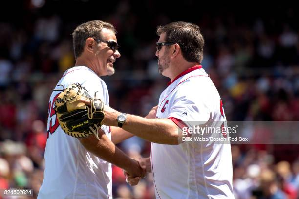 Former Boston Red Sox player Mike Lowell shakes hands with Jason Varitek after throwing out the ceremonial first pitch during a 2007 World Series...