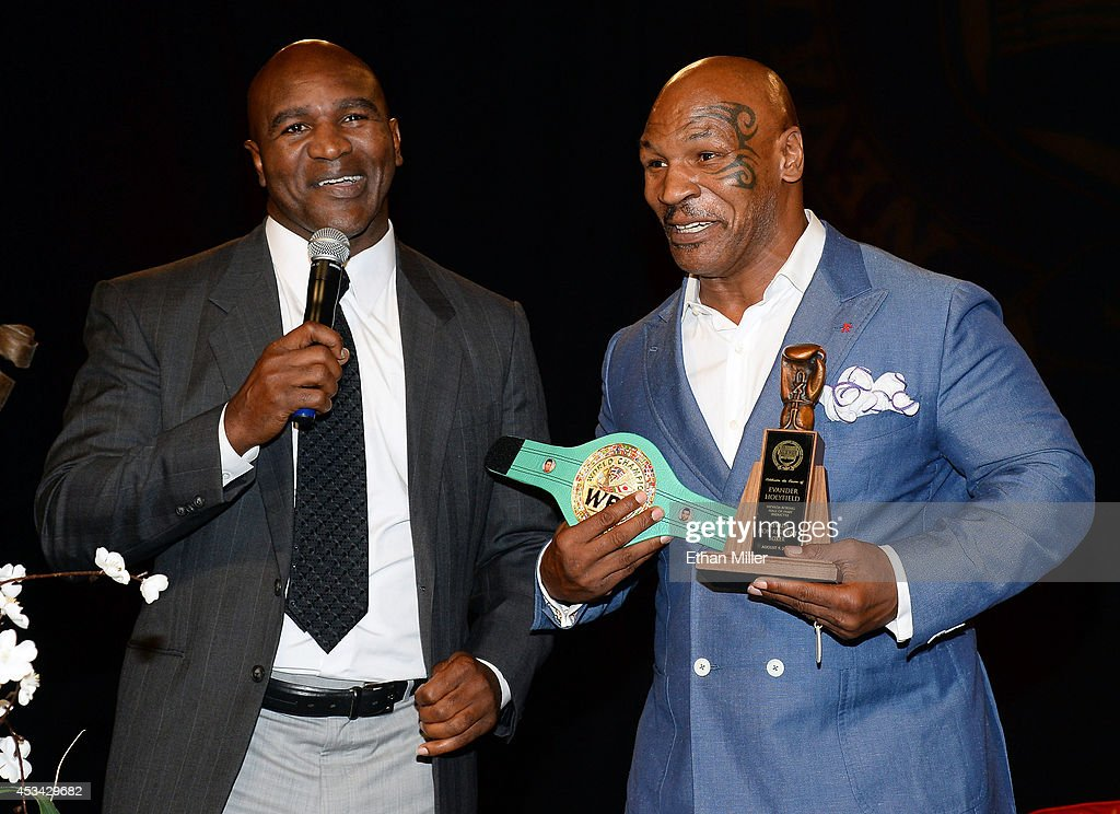 Former boxer Evander Holyfield (L) jokes around with former boxer Mike Tyson as he inducts Holyfield into the Nevada Boxing Hall of Fame at the second annual induction gala at the New Tropicana Las Vegas on August 9, 2014 in Las Vegas, Nevada.