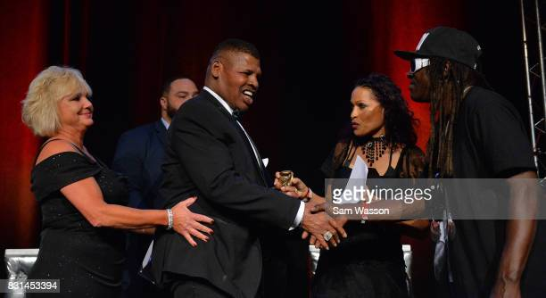 Former boxer Leon Spinks is greeted by rapper Flavor Flav as Spinks is inducted into the Nevdada Boxing Hall of Fame at the the fifth annual...