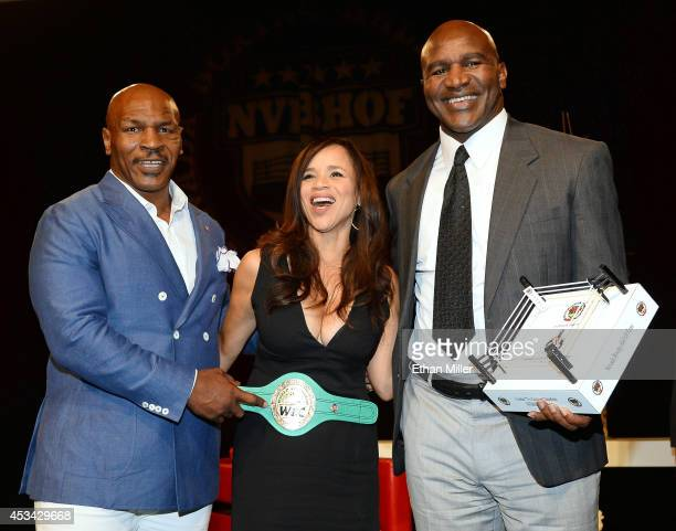 Former boxer Mike Tyson actress and emcee Rosie Perez and former boxer Evander Holyfield pose onstage after Tyson inducted Holyfield into the Nevada...